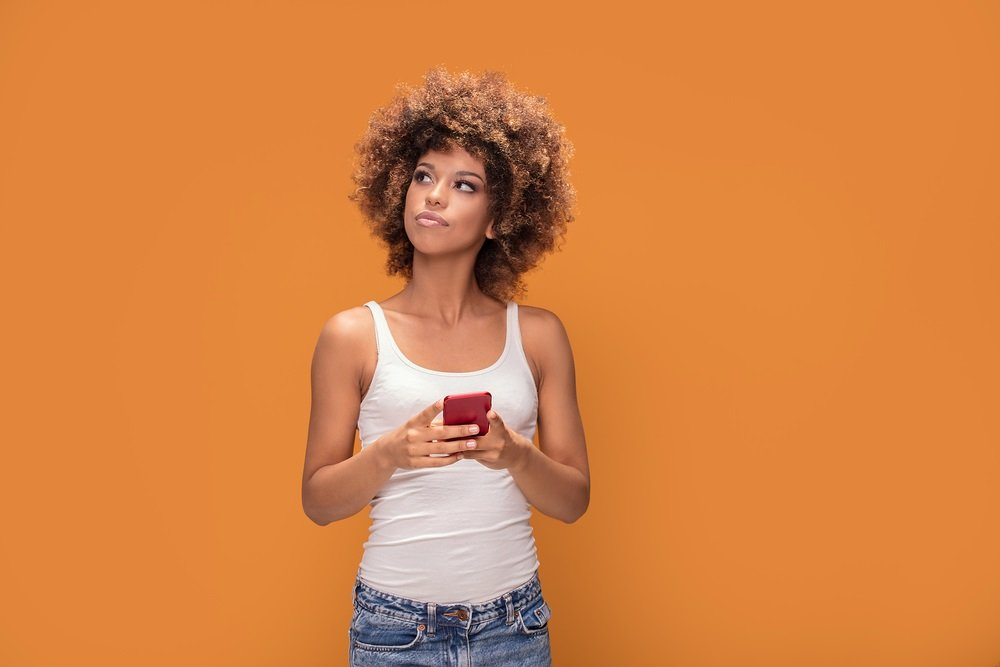 Young woman with mobile phone leaving a review